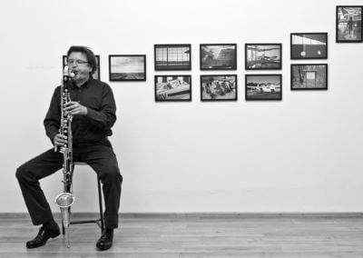 Udo Schindler mit Baßklarinette vor einer Bilderwand