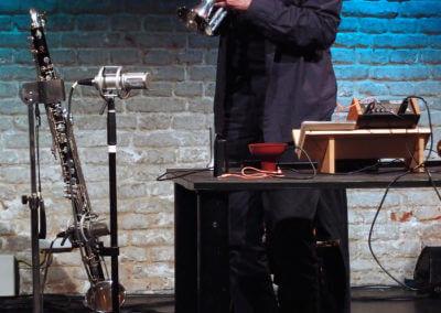 Udo Schindler bläst in ein Kornett, daneben eine Bassklarinette und ein Analog-Synthesizer